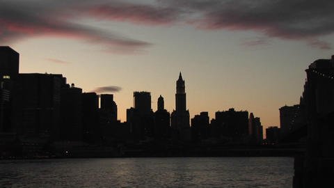 The camera pans from the Brooklyn Bridge to the skyscrapers of Manhattan silhouetted at the golden-h Footage