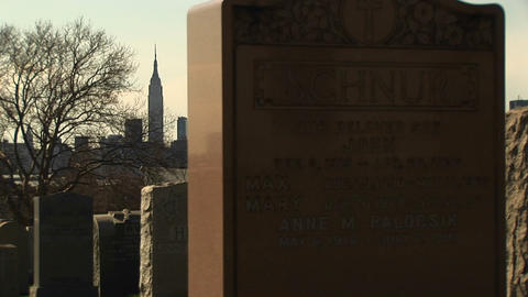 The camera pans left past old headstones in a cemetery with the modern-day Manhattan skyline in the Footage