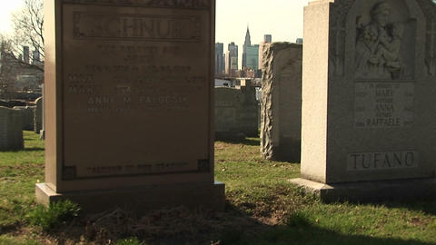 The camera pans back and forth in this cemetery with the skyline of New York in the background Footage