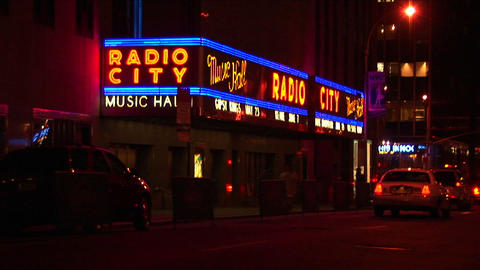 Cars pass by the brightly lit Radio City Musical Hall marquee at night Footage