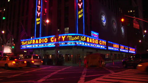The camera pans down the Radio City Music Hall signs and marquee to street level with taxis and pede Footage