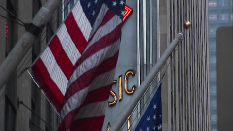 Camera pans down City Music Hall marquee and American flags Stock Video Footage