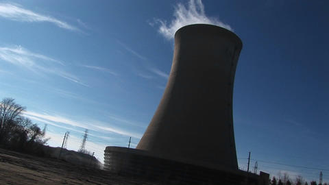 Steam rises from the top of a nuclear power plant in this tilted shot Footage