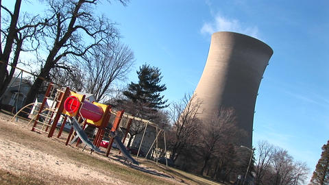 The camera tilts to show a playground and nuclear-power plant near each other Footage