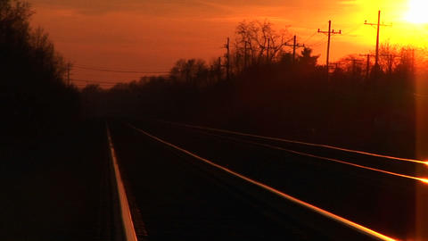 A brilliant golden-hour sky casts its reflection on railroad tracks stretching towards the horizon Footage