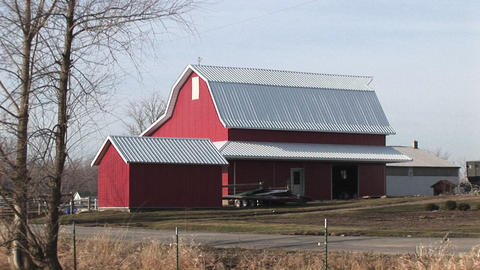 This bright red barn stands out on this rather cloudy winter day Footage