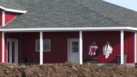 A red house has two small clothes-lines with laundry... Stock Video Footage