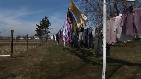 Colorful laundry hangs outdoors to dry in a rural community Stock Video Footage