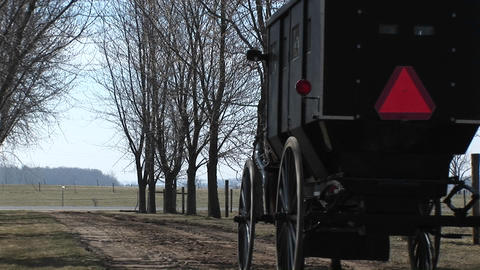 An Amish horse and buggy head toward the main road with... Stock Video Footage