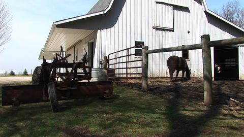 A piece of farm equipment is parked on the grass near the barn with the horse in the corral Footage