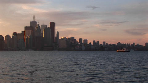 Waterfront perspective of the Toronto skyline during the golden-hour with boats moving across Lake O Footage