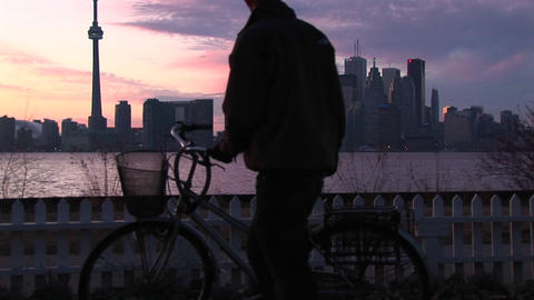 A tourist removes a bicycle parked on one of the Toronto islands at golden-hour with Lake Ontario, t Footage