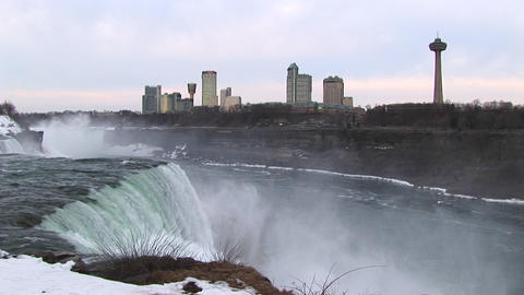 The tourist hotels and viewing tower look stark against a pale sky with Niagara Falls in the foregro Footage