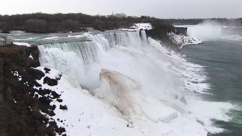A look at Niagara Falls in winter with frozen mist forming giant ice chunks Footage
