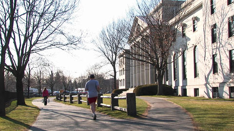 A student jogs through campus Stock Video Footage