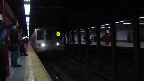 A subway train arrives at the station while passengers wait to ride Footage
