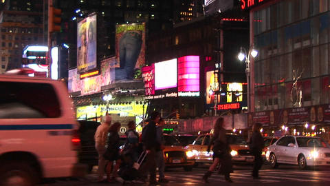 Medium-shot of Times Square with pedestrians and turning traffic Footage