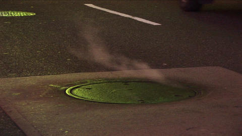 Medium-shot of steam rising from a manhole cover Stock Video Footage