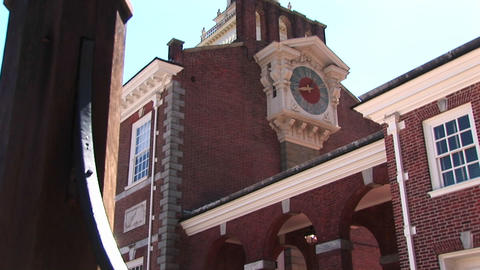 The camera pans up from street-level to a clock-face on the side of Independence Hall, Philadelphia Footage