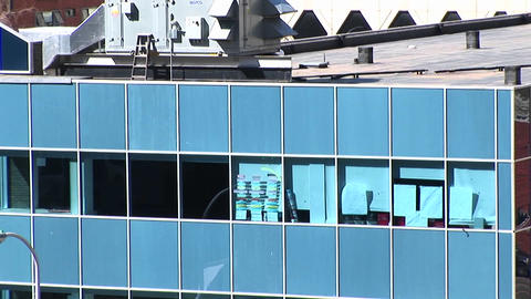 A blue, urban, office building has some of its windows covered with papers or notices on the interio Footage