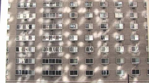 A large apartment or hotel exterior provides an interesting background pattern from reflected sunlig Footage