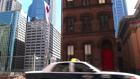 Skyscraper construction encroaches on a typical New York brownstone with a bright red door and an em Footage