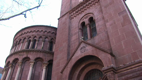 The camera pans up for a worms-eye view of the facade of a red stone church to focus on ornamentatio Footage