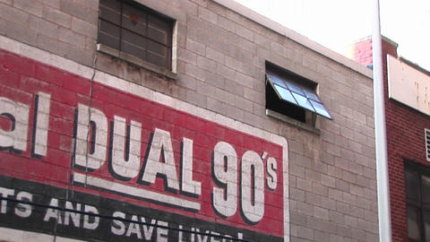 The camera zooms in on an open window past advertising on an old building Footage