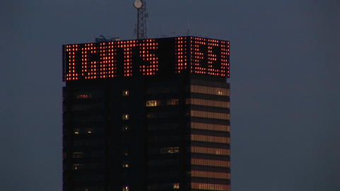 The camera pans up a skyscraper topped with a revolving marquee announcing stock market and other ne Footage