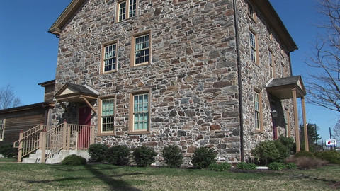The camera pans up the exterior of a three-story fieldstone house with two entrances Footage