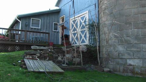 A sideview of modest home and barn-like door of the garage Footage