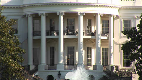 The camera pans up to show several people walking on the second floor balcony of the White House Footage