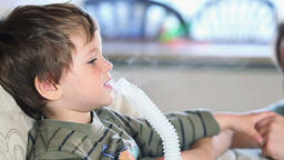 Mother and little boy using nebulizer to inhale medicine, shallow DOF, panning Footage