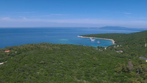 Aerial - Flying above dense pine forest hill with a view at a bay Footage
