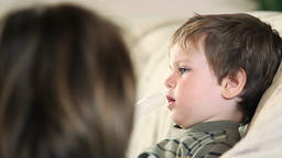 Sick little boy and mother using nebulizer to inhale the medicine panning Footage
