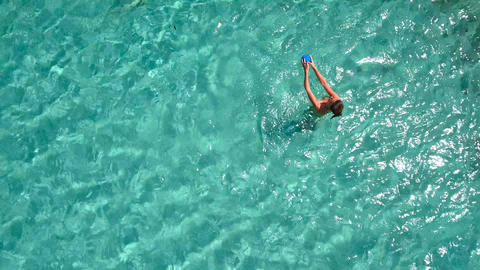 Aerial - Top down view of adult couple tossing a ball in the sea Footage