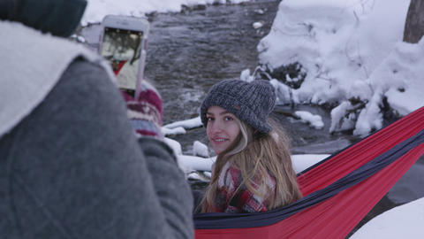Girl smiling for photo as she sits in hammock outside in the snow Live Action