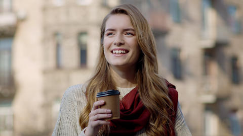 Pretty woman drinking coffee outdoors. Hipster girl enjoying hot drink on city Live Action