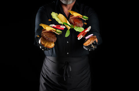 chef in a black shirt, apron and latex black gloves stands on a Fotografía