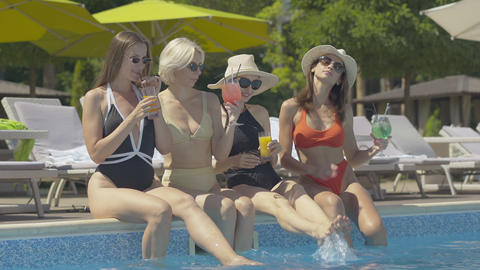 Portrait of happy relaxed tourists sitting on poolside with drinking glasses and Live Action
