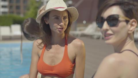 Portrait of gorgeous Caucasian adult woman in sun hat talking with friend Live Action