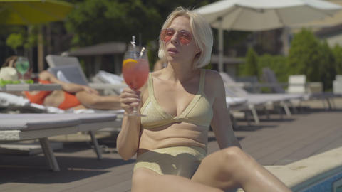 Portrait of confident relaxed blond woman drinking cocktail at luxurious resort Live Action