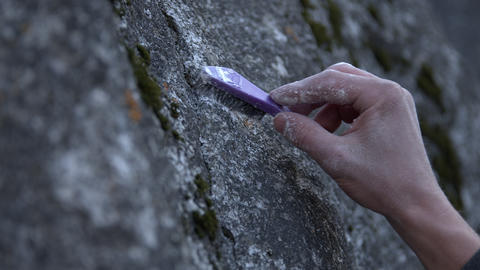View of rock as person brushes chalk on to it Live Action