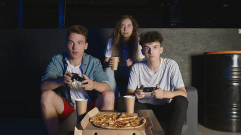 Young cheerful friends are having fun with video game at party in house. They GIF