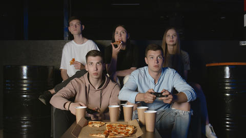 Young men having fun with video game at party in house while friends watching GIF