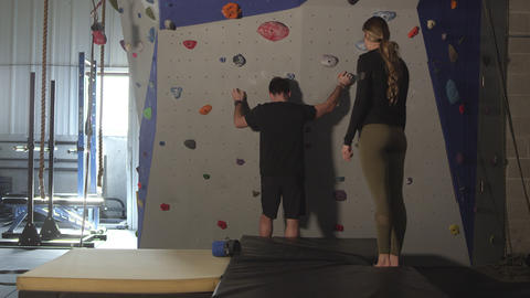 Couple in gym working out on rock climbing wall Live Action