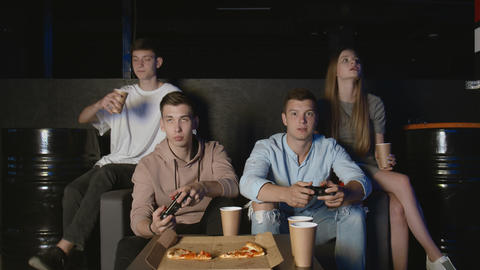 Friends having fun with video game at home, young men winning doing high-five GIF
