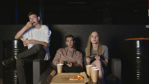 Cheerful company plays in the console game, girl against boy. Eats pizza Live Action