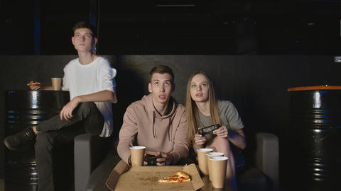 Group of concentrated friends plays in the console game, woman against man. Eats GIF