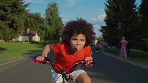 Cute mixed race boy having fun riding bike in park Live Action